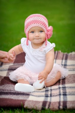 Baby girl in the park in a pink knitted hat