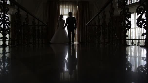 Silhouettes of the bride and groom in the hall in front of the window