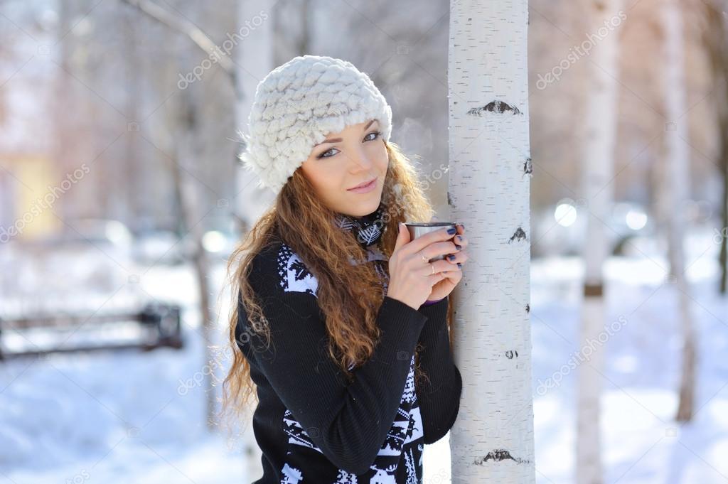 beautiful girl drinking hot tea in winter outdoors