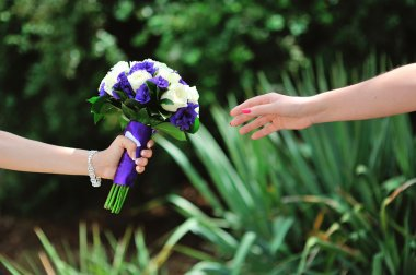 groom gives his bride a bouquet