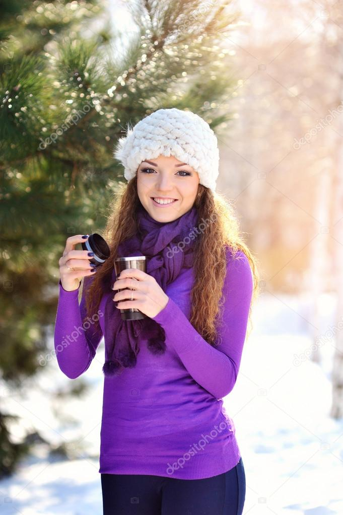 beautiful young woman having a cup of tea in the winter sun