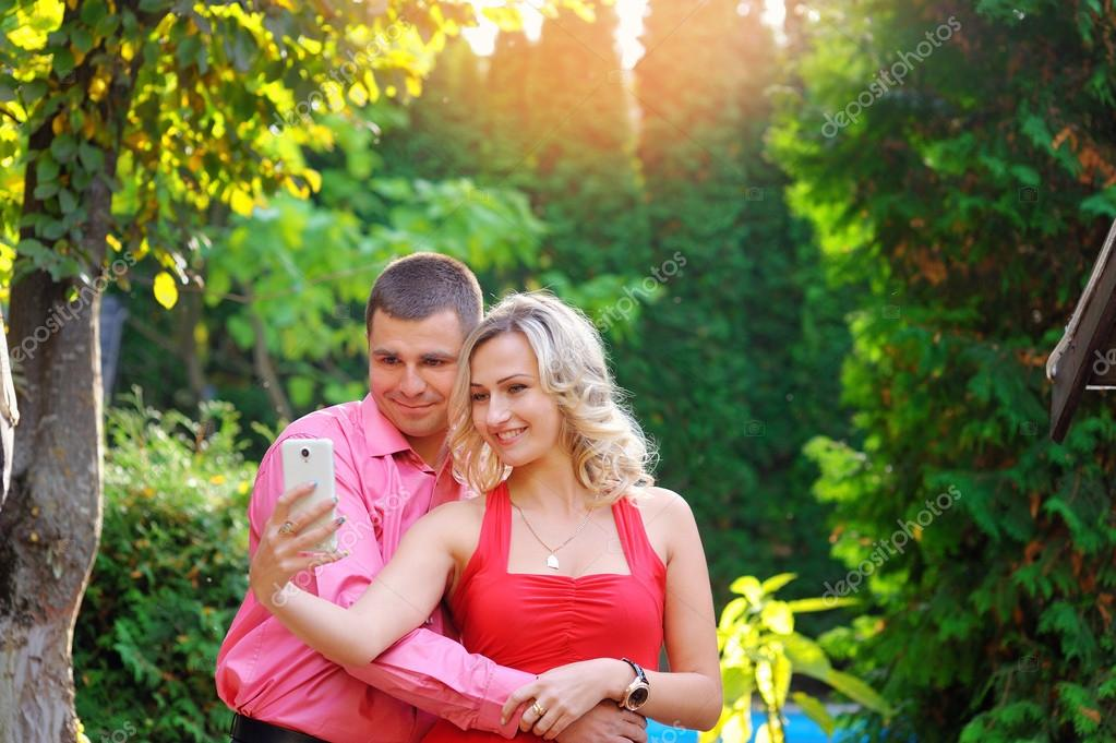 Affectionate young couple taking pictures using a smart phone at