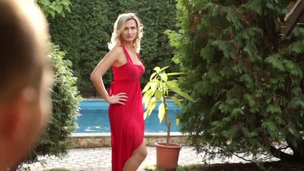 a72cfe350981fd Meisje in een rode jurk poseren in het park — Stockvideo © timonko ...