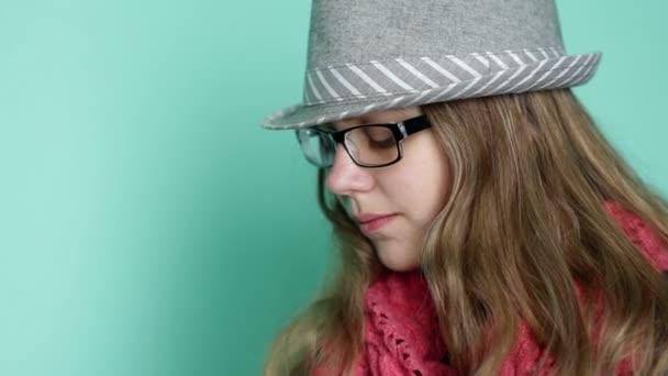 Krásná dívka s brýlemi klobouk na pozadí tyrkysové stěny