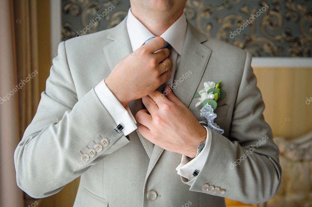a9b3bedc90b6 Man in a suit straightens his tie with cufflinks on their sleeves. — Εικόνα  από ...