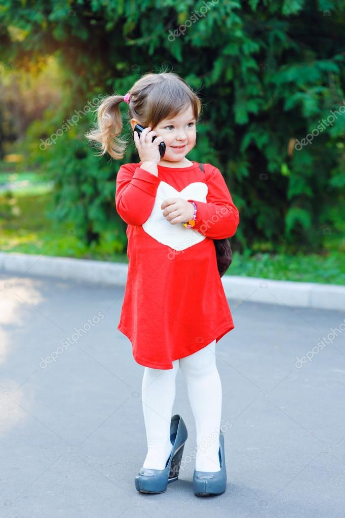 little girl in big shoes talking on the phone