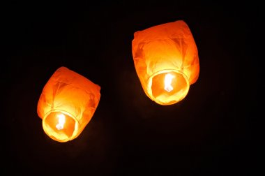 two sky lanterns in the sky at night