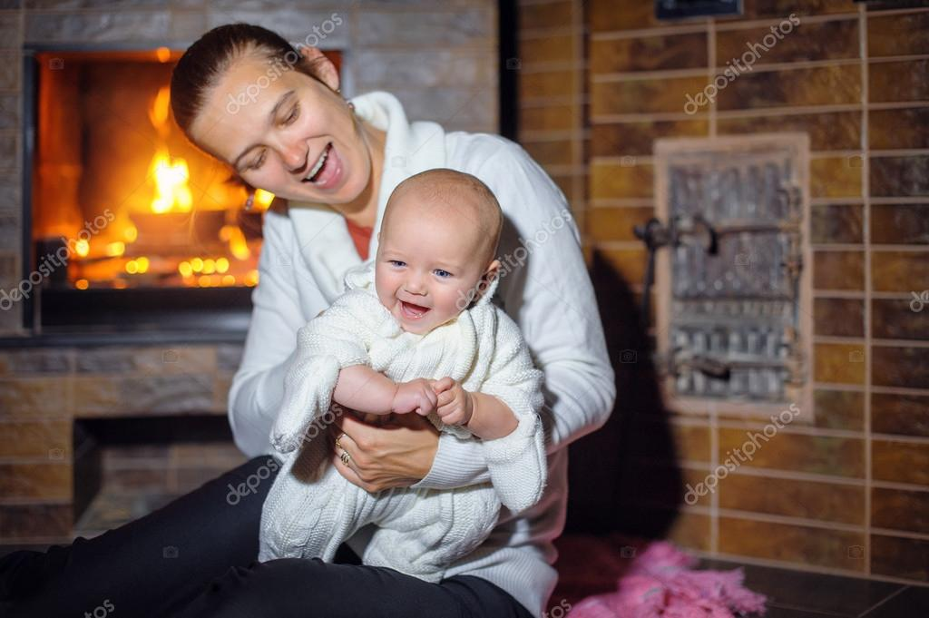 Happy mother with a baby girl by the fireplace