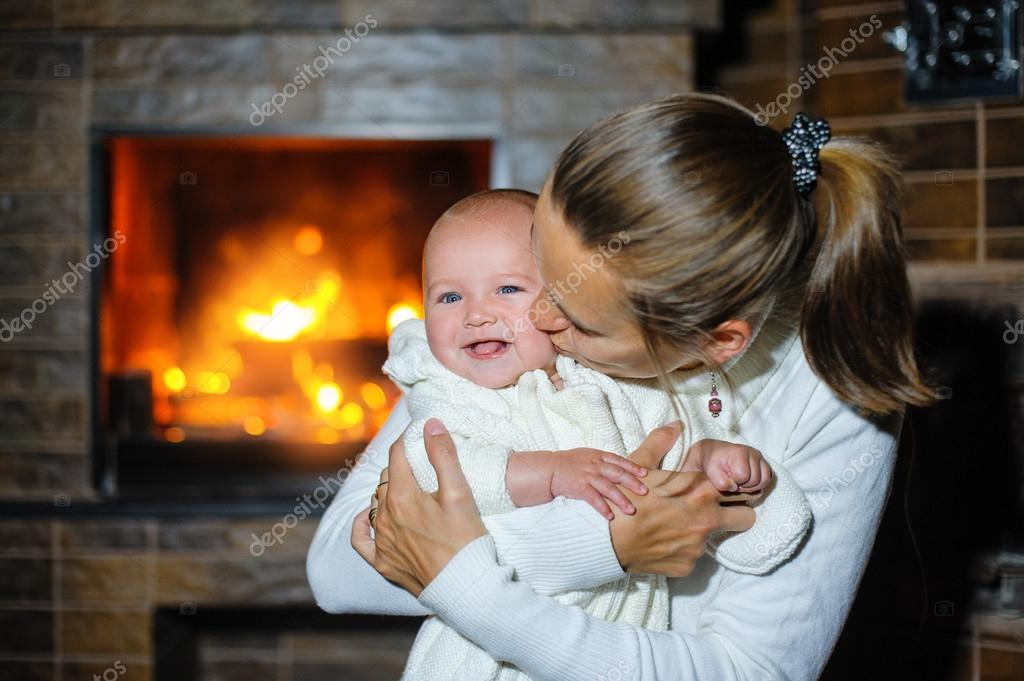 Happy mother kissing baby girl by the fireplace