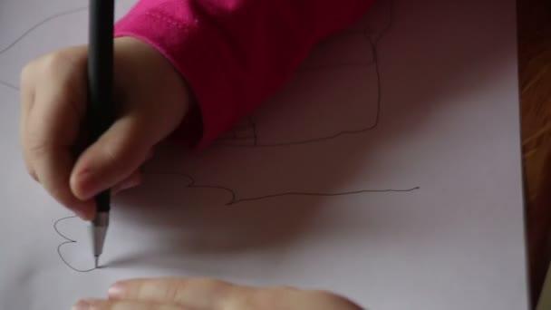 Malá holčička kreslí tužkou na papíře