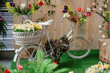 Decorative baskets with flowers on a white bicycle
