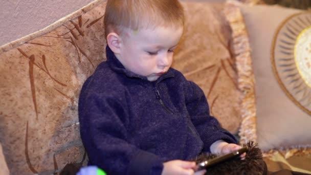 Malý chlapec sedí na gauči a sledovat kreslené na vašem smartphone