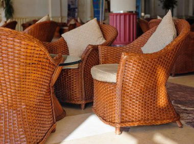 Brown wooden chairs with cushions in the lobby