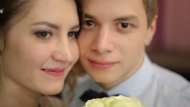 Nevěsta a ženich se drží svatební kytici bílých růží