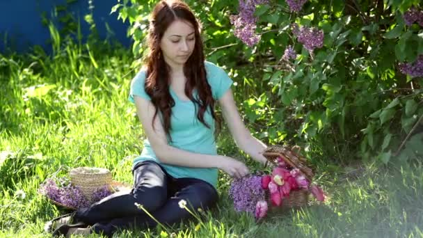 Beautiful woman with a bouquet of lilac sitting in the spring park on the grass