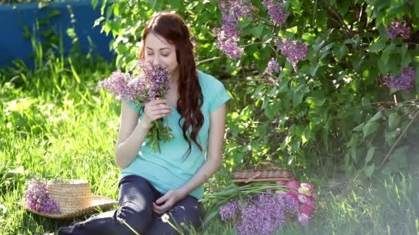 Krásná žena s kytici šeříku sedí v parku na jaře na trávě