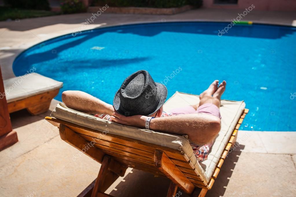 Homme au chapeau allong sur un transat au bord de la for Bord de la piscine
