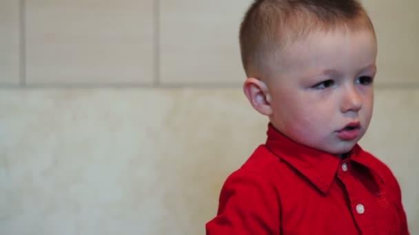 smutný malý chlapec v červené košili