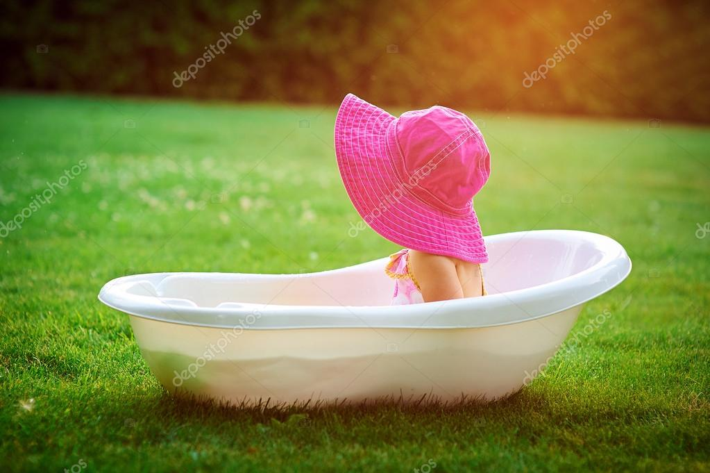 Little girl in a red hat bathed in the bath