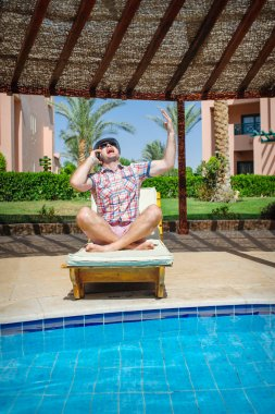 man in a hat sitting by the pool and talking on the phone