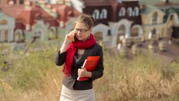 beautiful woman in glasses with red folder on the phone