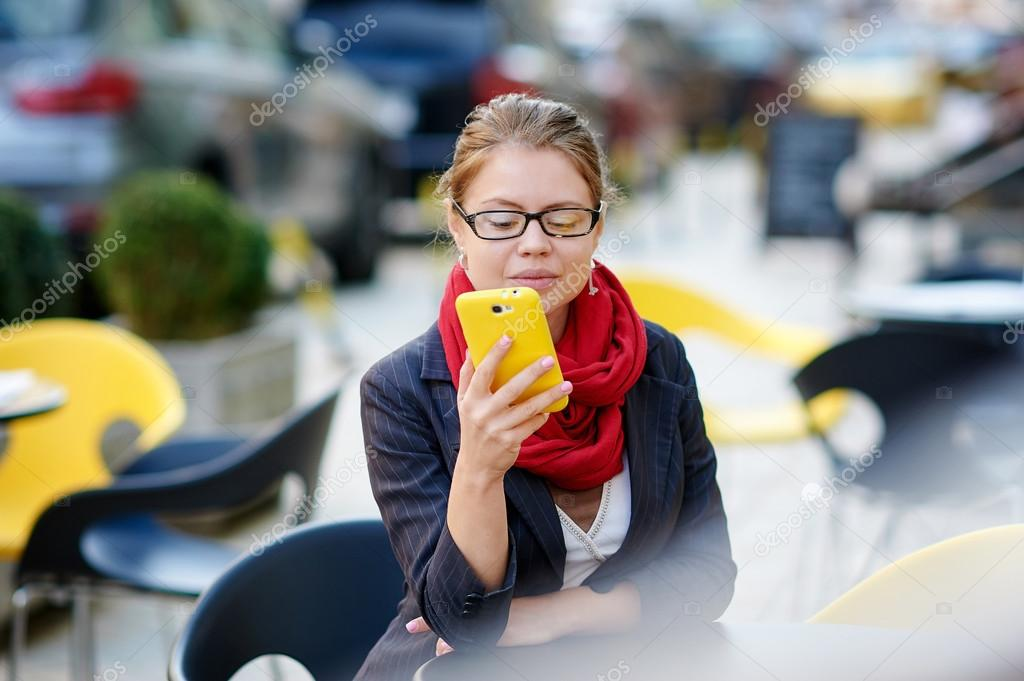 woman with glasses sitting in a cafe and looking in the phone
