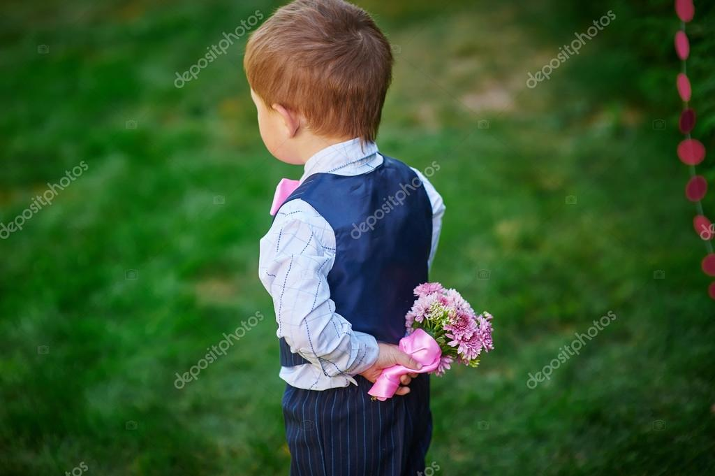 Little boy holding a bouquet of flowers behind his back