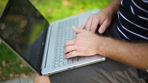 Fiatal ember ül a padon, ölébe laptop