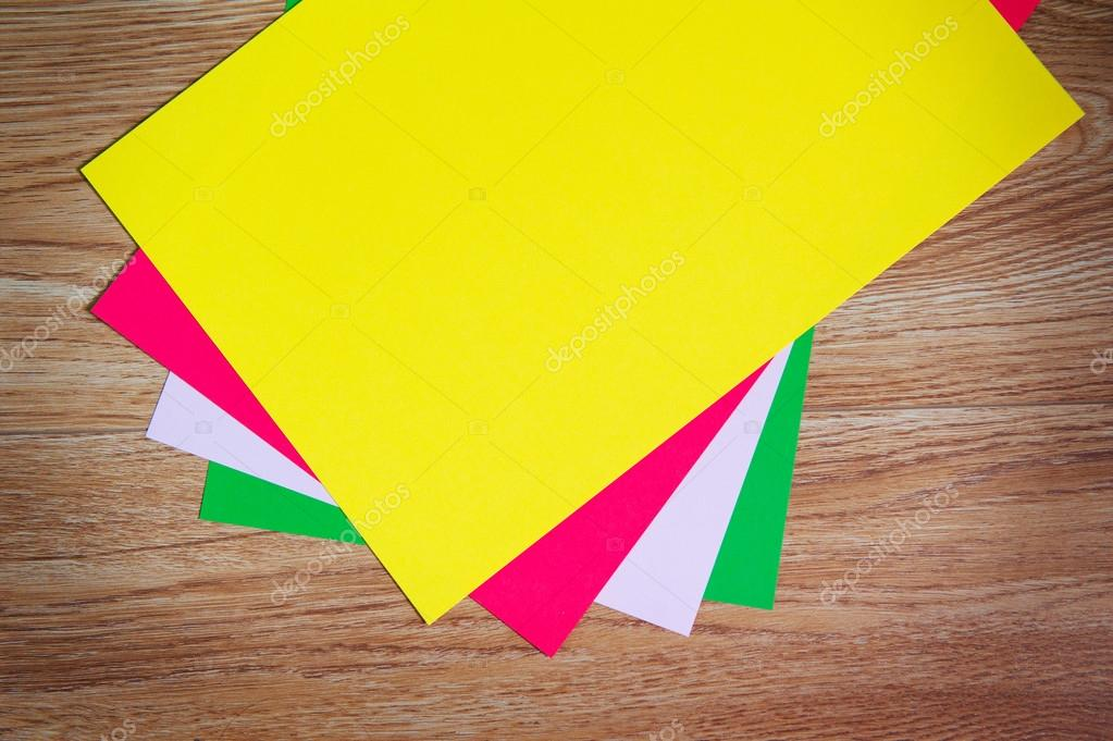 colored sheets of paper stacked on a wooden floor — Stock Photo ...