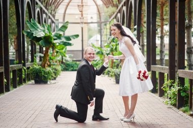 groom kneels on one knee in front of a happy bride