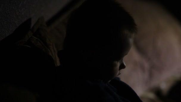 niño se sienta en el sofá en el cuarto oscuro — Vídeo de stock ...