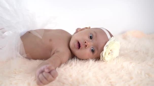 Schöne neugeborene Mädchen liegt in einem Rock und mit einer Schleife auf dem Kopf