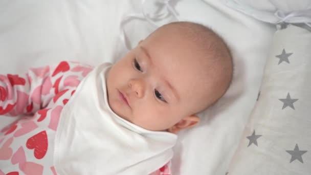 portrét šťastného novorozence ležícího na posteli