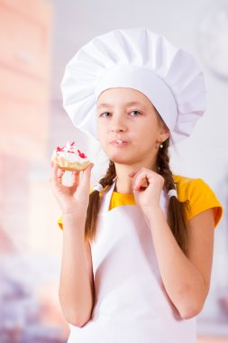 Girl in apron and cap eat delicious cookies