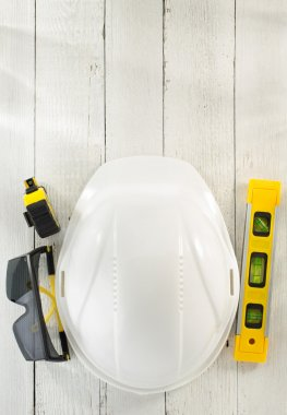 hardhat and safety glasses on wood