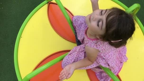 Zeitlupe eines Mädchens auf einem Karussellspielplatz.