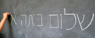 Little child hand writes Hello First Grade greetings in Hebrew