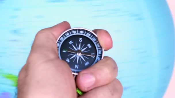 Man hand holds a compass against a globe