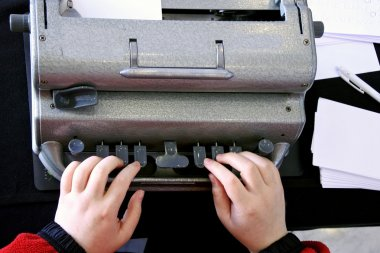 Blind person typing on a braille typing machine