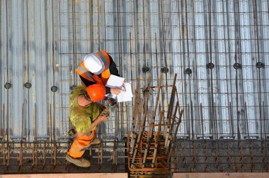 Civil engineer inspecting the work progress of a worker in a con