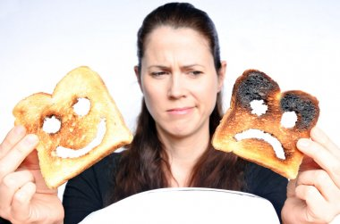 Woman looks a two different slices of toast bread