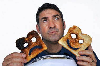 Man looks up and holds two different slices of toast bread