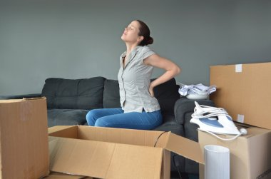 Woman suffers from back pain due to unpacking boxes