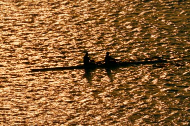 Silhouette of sportsmen on row boats