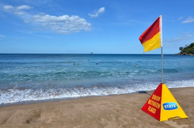Red and yellow flag near sea
