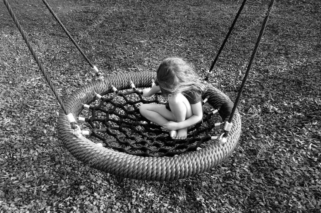 Sad girl on a swing at playground