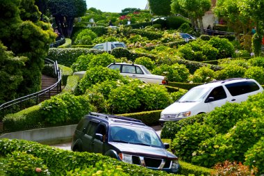 Cars drive down Lombard Street switchback in San Francisco CA