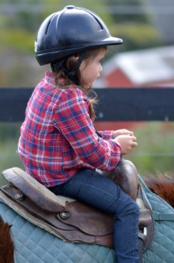 Little girl ride a horse during horse ridding lesson