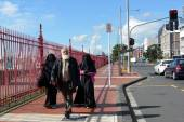 Muslim man walks with two muslim woman with fully body cover (Bu