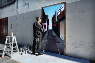 Graffiti artist paint a mural on a wall